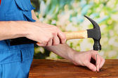 Builder hammering nails into board on natural background — Stock Photo
