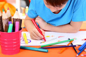 Cute little boy drawing in his notebook — Stock Photo