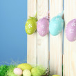 Art Easter background with eggs hanging on fence — ストック写真