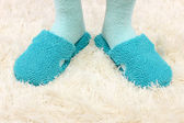 Female legs in color slippers, on carpet background — Stock Photo