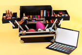 Open case with cosmetics on yellow background — Stock Photo