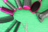Comb brushes, hairdryer and cutting shears,on color background — Stok fotoğraf