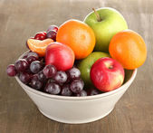 Bowl with fruits, on wooden table — Foto de Stock
