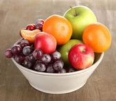 Tazón de fuente con frutas, en mesa de madera — Foto de Stock