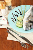 Fish dorado with lemon on plate on wooden table close-up — Stock Photo