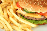 Tasty cheeseburger with fried potatoes, close up — Stock Photo