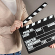 Movie production clapper board in hands on grey background — Stock fotografie