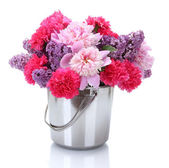 Beautiful spring flowers in metal bucket isolated on white — Stock Photo