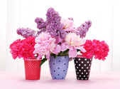Spring flowers in cups on table on white wooden background — Stock Photo