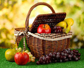 Picnic basket with fruits on grass on bright background — Stock Photo