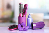 Hair brushes, hairdryer and cosmetic bottle in beauty salon — Stock Photo