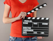 Movie production clapper board in hands on grey background — Stock Photo