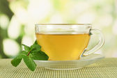 Cup of tea with mint on table on bright bacground — Stock Photo
