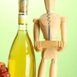 Mannequin with corkscrew and wine bottle, on green background — Stock Photo