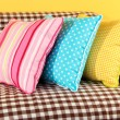Colorful pillows on couch on yellow background — Stock Photo