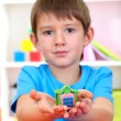 Cute little boy holding hand-made plasticine hourse over desk — Lizenzfreies Foto