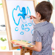 Little boy painting paints picture on easel — Stock Photo #20102795