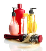 Comb brush with hair and cosmetic bottles, isolated on white — Stock Photo