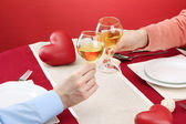 Romantik çift onların şarap bardakları restaurant masa üzerinde toasting eller — Stok fotoğraf