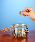 Saving, female hand putting a coin into glass bottle, on color background — Stock Photo