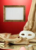 Máscara branca, moldura vazia e tecido de seda dourado, sobre fundo vermelho — Foto Stock