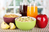 Delicious and healthy cereal in bowls with juice and fruit on table in room — Stock Photo