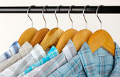 Shirts with ties on wooden hangers on light background — Stock Photo