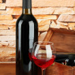 Bottle of wine and glass on table on brick wall background - Stock Photo