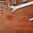 Bolts, screws, nuts and wrench on wooden table — Stockfoto
