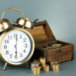 Stock Photo: Alarm clock with coins in chest on grey background