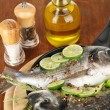 Two fish dorado with lemon on pan on wooden table close-up — Stock Photo