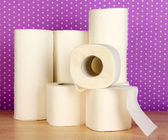 Rolls of toilet paper on purple with dots background — Stock Photo