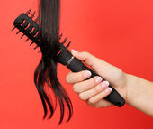 Dark curls brushing comb on color background — Stock Photo