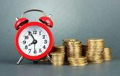 Reloj despertador con monedas en fondo gris — Foto de Stock