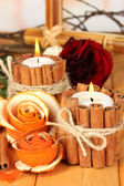 Decorative rose from dry orange peel and burning candles on wooden table — Stock Photo