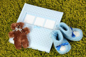 Baby photo album on green carpet — Stock Photo