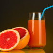 Delicious grapefruit juice in glass and grapefruit next to it on dark orange background — Stock Photo