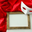 White mask, empty frame and red silk fabric, isolated on white — Stock Photo