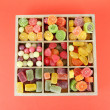 Multicolor candies in wooden box, on color background - Stockfoto