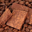 Chopped chocolate with cocoa, on coffee beans background - Photo