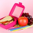 Lunch box with sandwich,fruit and stationery on pink background - Foto Stock