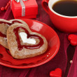 Chocolate cookies in form of heart with cup of coffee on pink tablecloth close-up — Stock Photo