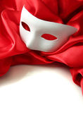 White mask and red silk fabric, isolated on white — Stock Photo