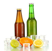 Beer bottles in ice isolated on white — Stock Photo