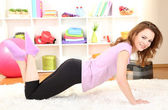 Young woman doing fitness exercises at home — Stock Photo