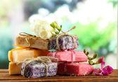 Naturalne mydła ręcznie robione, na drewnianym stole, na zielonym tle — Zdjęcie stockowe