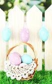 Art Easter background with eggs hanging on fence — Stock Photo
