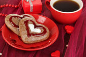 Chocolate cookies in form of heart with cup of coffee on pink tablecloth close-up — Photo