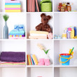 Stock Photo: Beautiful white shelves with different baby related objects