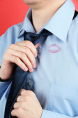 Lipstick kiss on shirt collar of man, on red background — Stock Photo